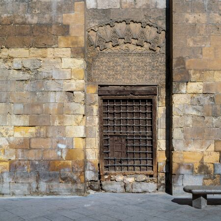 Daylight shot of grunge wooden window with decorated iron grid over stone bricks wall and marble garden bench, Moez Street, Cairo, Egypt Stock Photo - 131870536