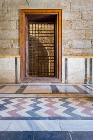 Recessed wooden window with decorated iron grid over stone bricks wall and decorative colorful floor at public historic mosque of Sultan Barquq, El Moez Street, Old Cairo, Egypt Stock Photo - 131870126