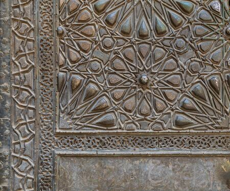 Ornaments of the bronze-plate ornate door of Sultan Barquq mosque, ancient public historic mosque in Old Cairo, Egypt Stock Photo - 131870546