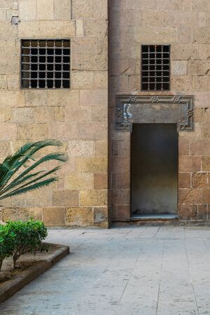 Ancient external old decorated bricks stone wall with two windows and opened door leading to Ottoman era Beit El Sehemy historical building, Cairo, Egypt Stock Photo - 132034513