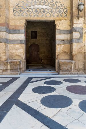 Stone bricks wall and opened door leading to passage at the courtyard of public historic mosque of Sultan Barquq, Moez Street, Old Cairo, Egypt Stock Photo - 132039503