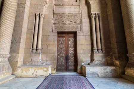 External old decorated bricks stone wall with arabesque decorated wooden door framed by stone ornate cylindrical columns leading to al Rifai Mosque, Old Cairo, Egypt Stock Photo - 133246634