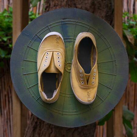 Shabby ruined yellow shoes with stitches attached to grunge green dartboard game board on tree trunk in garden Stock Photo - 135043226