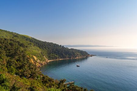 View from the top of mountains of Buyukada island, one of the Princess Islands, Adalar, Marmara Sea, Istanbul, Turkey, with green woods, calm sea, and clear sky at sunset time Stock Photo