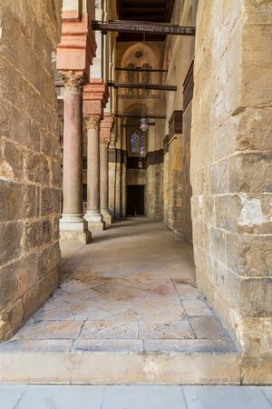 Passage at Sultan Qalawun Mosque with stone columns, colored stained glass windows and wooden door, Cairo, Egypt Stock Photo - 135069605