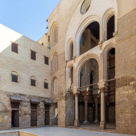 Main courtyard of public historic mosque of Sultan Qalawun with huge arches, wooden doors and decorated windows, Cairo, Egypt Stock Photo - 135069634
