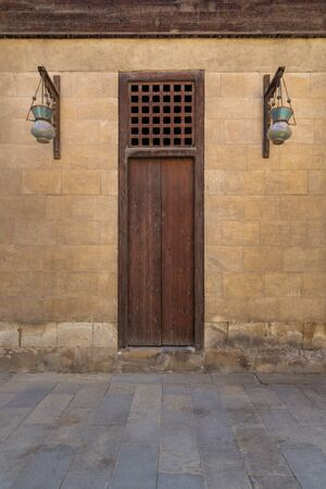 Wooden closed door and two Arabic glass street lanterns hanged on a wooden pole in old stone bricks wall, Medieval Cairo, Egypt