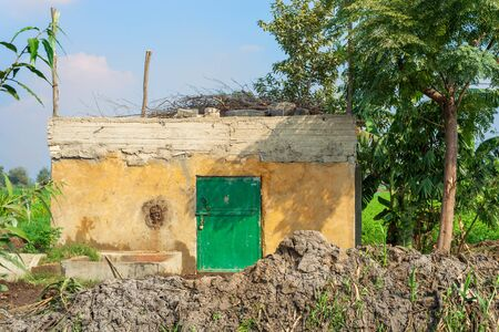 Abandoned exotic yellow rocked hut with single green wooden grunge door, tropical green trees and lots of clay at village on sunny day Stock Photo