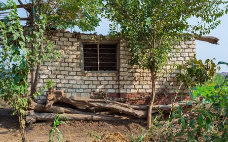 Abandoned exotic white stones bricks rocked hut with single iron rusted window and tropical green plants at village on sunny day