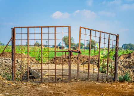Weathered old gate tied with rope and installed near heaps of soil against cloudy sky on sunny day on farm Stock Photo - 135135129