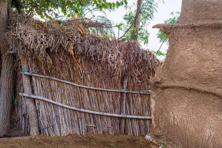 Exotic bamboo rocked hut without windows with straw roof and clay wall at traditional Egyptian village on sunny day Stock Photo - 135136415