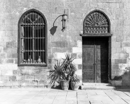 Black and white shot of fold abandoned stone bricks wall with arched wooden door and window covered with wrought iron bars and lantern, Cairo, Egypt Stock Photo - 135592492