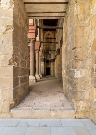 Passage at Sultan Qalawun Mosque with stone columns, colored stained glass windows and wooden door, Cairo, Egypt Stock Photo