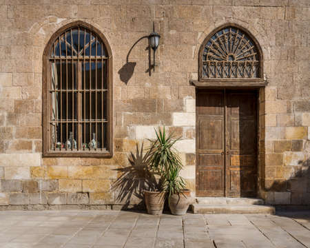 Facade of old abandoned stone bricks wall with arched wooden door and window covered with wrought iron bars and lantern, Cairo, Egypt