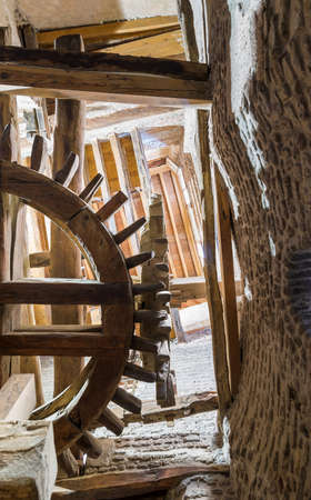 From below shot of aged water mill turning inside weathered mill building at Amir Taz palace, Medieval Cairo, Egypt