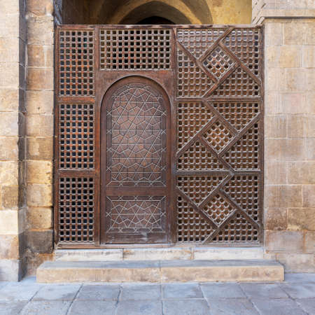 Interleaved wooden wall, known as mashrabiya, with wooden ornate door, Old Cairo, Egypt
