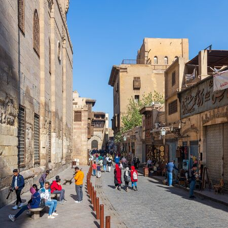 Cairo, Egypt- December 14 2019: Moez Street with local visitors Mosque of Sultan Barquq and Sabil-Kuttab of Katkhuda historic building at the far end, Gamalia district, Old Cairo Editorial