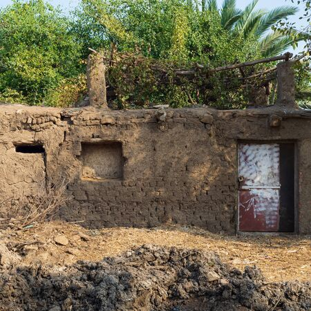 Facade of exotic clay rocked house without windows with tropical green plants on roof at village on sunny day Stock Photo - 136667403