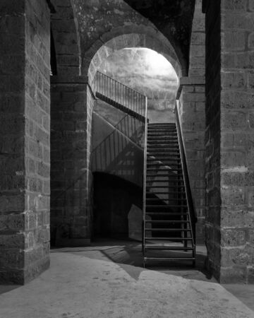 Black and white of dark abandoned underground passage with stone bricks columns and metal staircase, Medieval Cairo, Egypt Stock fotó