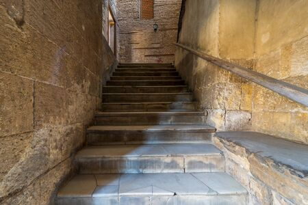 Day shot of old narrow stone staircase leading to stone bricks wall with closed window, Old Cairo, Egypt Stock Photo - 136667414