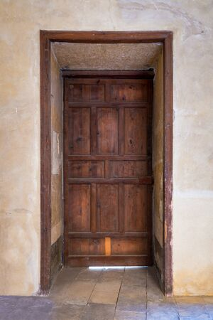 Recessed grunge wooden aged closed door on grunge stone wall, Medieval Cairo, Egypt Stock Photo - 136441547