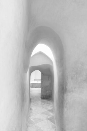 Black and white narrow archway of aged building with smooth shabby walls and tiled floor Stock Photo - 136667420