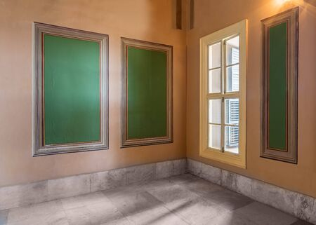 Three beautiful elegant rectangular green frames with ornate border and wooden window with green shutters on orange wall with white marble floor, in abandoned old building Stock Photo - 136680950