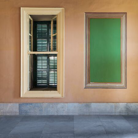 Beautiful elegant rectangular green frame with ornate border and narrow window with closed green shutter on orange wall with white marble floor, in abandoned old building Stock Photo - 136681080