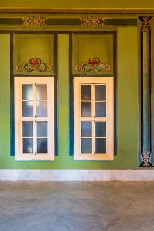Two narrow closed windows and beautiful elegant carved frames on green wall with ornate border and white marble tiled floor, in abandoned building Stock Photo - 137053804