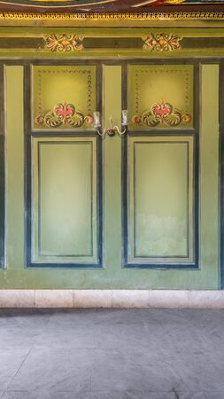 Beautiful elegant carved frames on green wall with ornate border with white marble tiled floor, in abandoned old building Stock Photo - 137053891