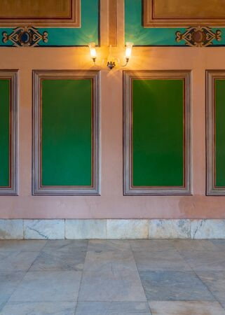 Beautiful elegant carved green frames on orange wall with ornate border and white marble tiled floor, in abandoned old building Stock Photo - 137064678