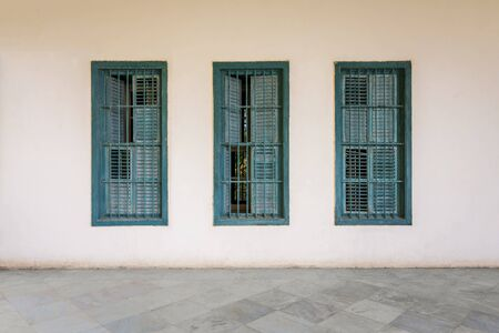 White wall with three grunge windows with wooden green shutters and wrought iron bars and white marble floor Stock Photo - 137064712