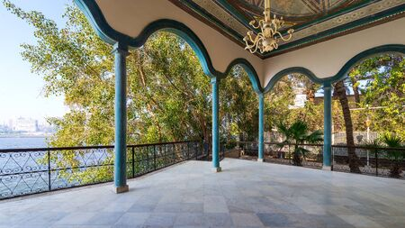 Covered terrace with green stone pillars, and marble floor fenced with metal forged fence and surrounded with green trees and river in sunny summer day Stock Photo - 137441643