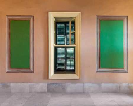 Narrow wooden window with closed green shutters mediating two beautiful elegant rectangular green frames on orange wall with white marble floor, in abandoned old building Stock Photo - 137441955