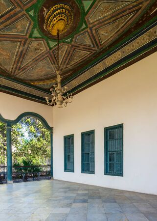 Covered terrace with decorated painted ceiling, green window shutters and marble floor fenced with metal forged fence in sunny summer day