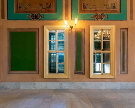 Two narrow wooden window with closed green shutters and beautiful elegant rectangular green frames on orange wall with white marble floor Stock Photo - 137442173