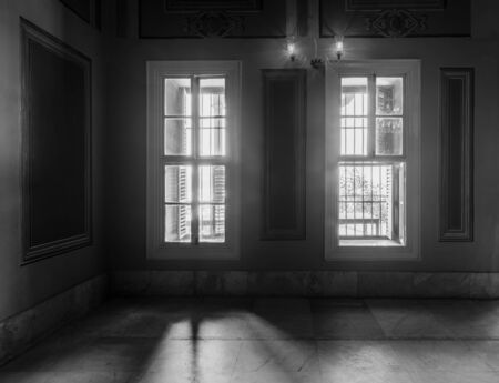 Black and white high contrast shot of two narrow windows, revealing strong light into dark room with white tiled marble floor