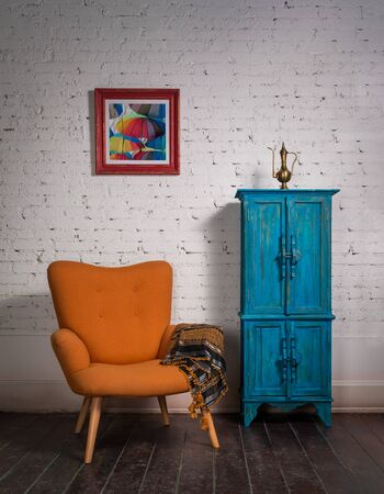 Living room corner with vintage orange armchair and ornate scarf beside blue cupboard on a red carpet, grunge dark wooden parquet floor and white bricks wall Stock Photo