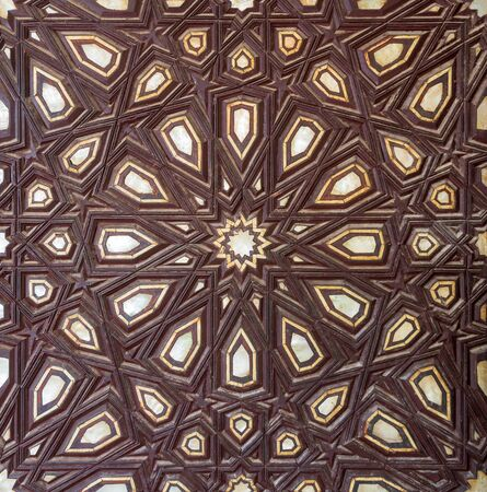 Closeup of wooden arabesque decorations tongue and groove assembled, inlaid with ivory and ebony, on old aged door, Rosetta City, Egypt Stock Photo