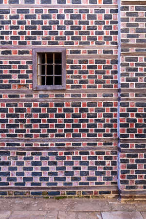 Wall with black and red bricks with white seam and small window with metal bars on cobblestone road