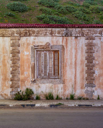 Exterior of aged house with weathered ornamental walls and shuttered window located under green hill and near asphalt road Stock Photo