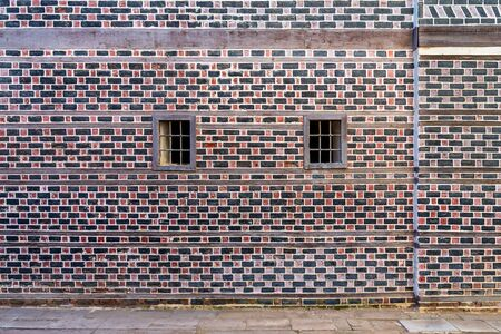 Wall with black and red bricks with white seam and two small adjacent windows with metal bars on cobblestone road Stock Photo