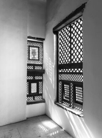 Black and white of corner of two Interleaved grunge wooden ornate windows - Mashrabiya - in stone wall at abandoned building
