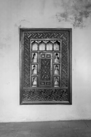 Black and white of wooden arabesque ottoman era cupboard with engraved decorations embedded in a grunge wall, Rosetta City, Egypt