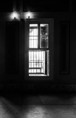 Black and white high contrast shot of narrow window, revealing strong light into dark room with illuminated lanterns and white tiled marble floor