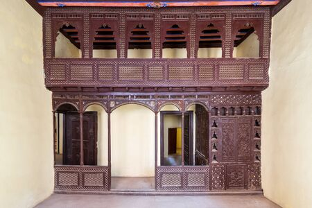 Oriental wooden engraved arabesque decorations with balcony installed in front of open doors inside empty spacious room Stock Photo