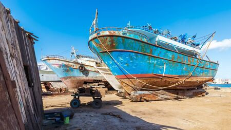 Old rusty vessels under repairing located on grungy dry dock in shipyard against blue sky on sunny day in old shipbuilding plant Stock Photo