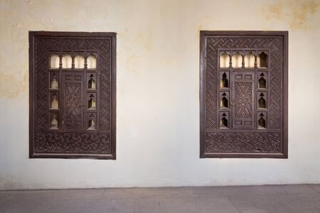 Two wooden arabesque ottoman era cupboards with engraved decorations embedded in a grunge wall