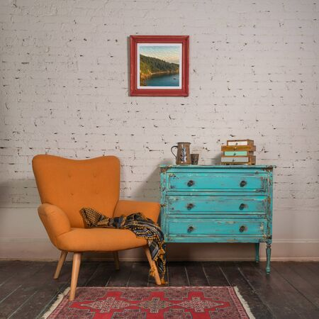 Bright orange retro armchair with plaid against white brick wall with shabby chic vintage turquoise cabinet in living room and hanged painting,