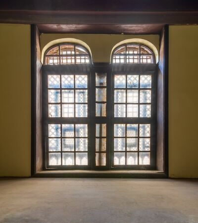 Large vintage window with ornament located inside empty room with yellow walls and wooden floor